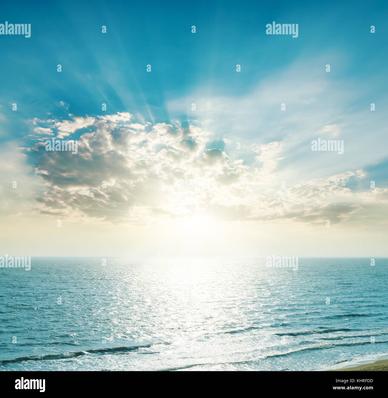 rising sun on the horizon, blue sea and clouds - Stock Image