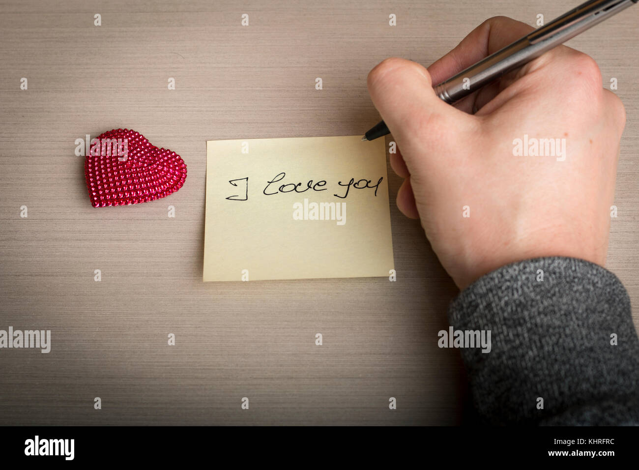 Man's hand writing I love you on sticky-note with little heart shaped figure beside - Stock Image