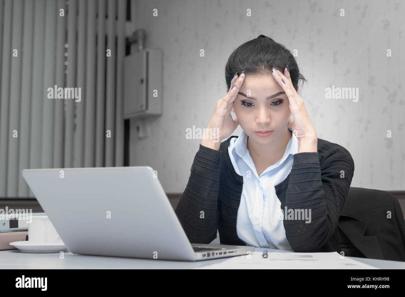 Exhausted asian business woman working at office desk with a laptop and touching her forehead, headache and stressful - Stock Image