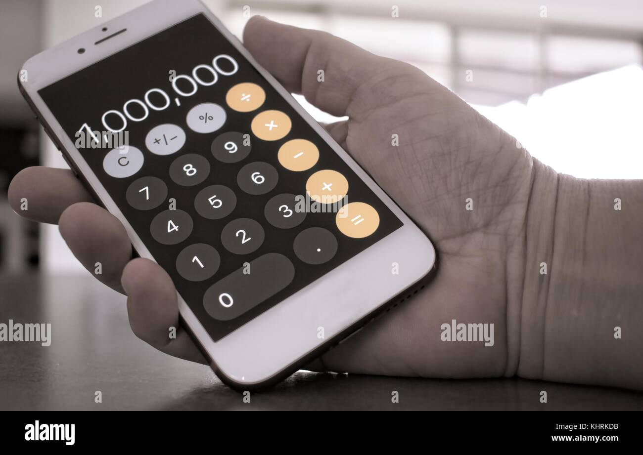 Woman's  hand holding mobile phone with the number 1000000 on display Stock Photo