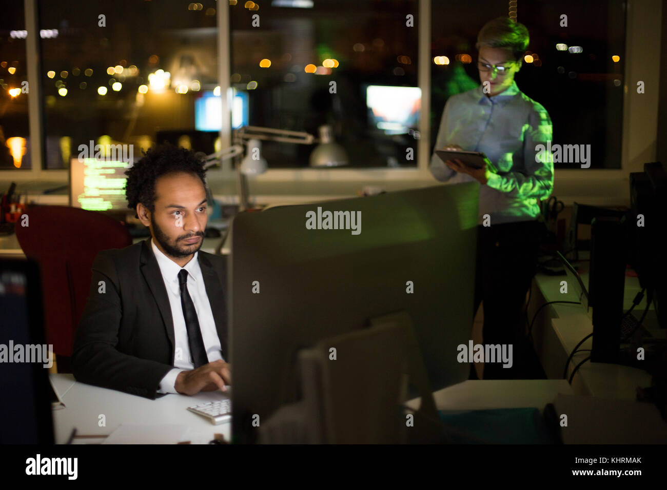 Busy dim open plan office: mixed race manager wearing stylish suit working on promising project with help of computer - Stock Image