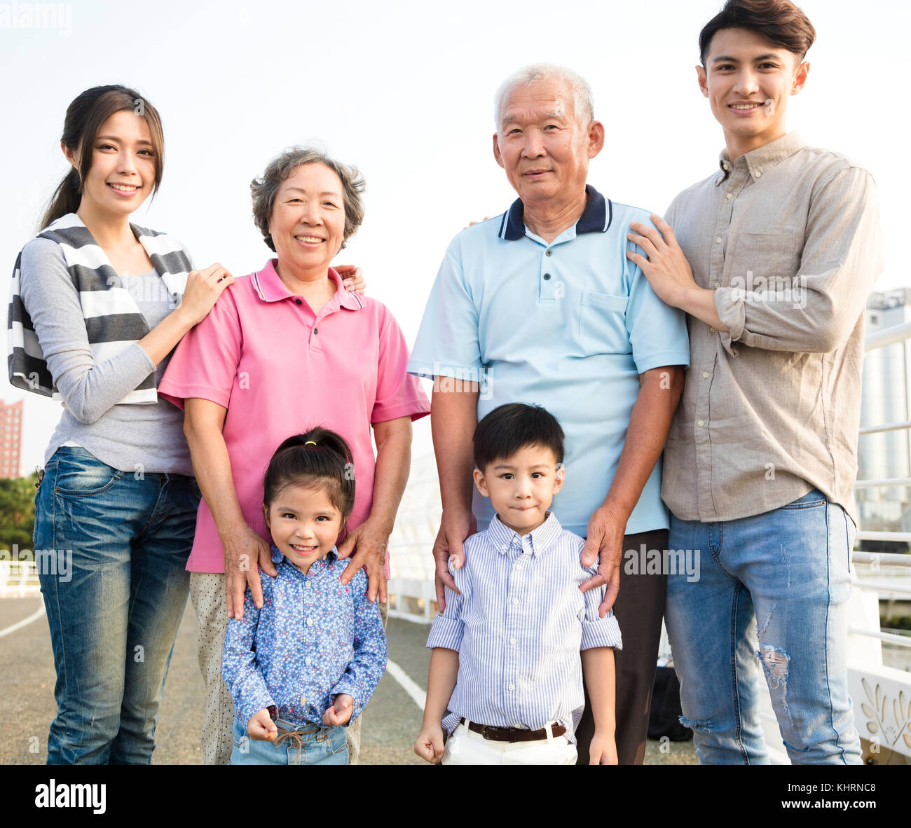 three generations family standing together outdoors - Stock Image