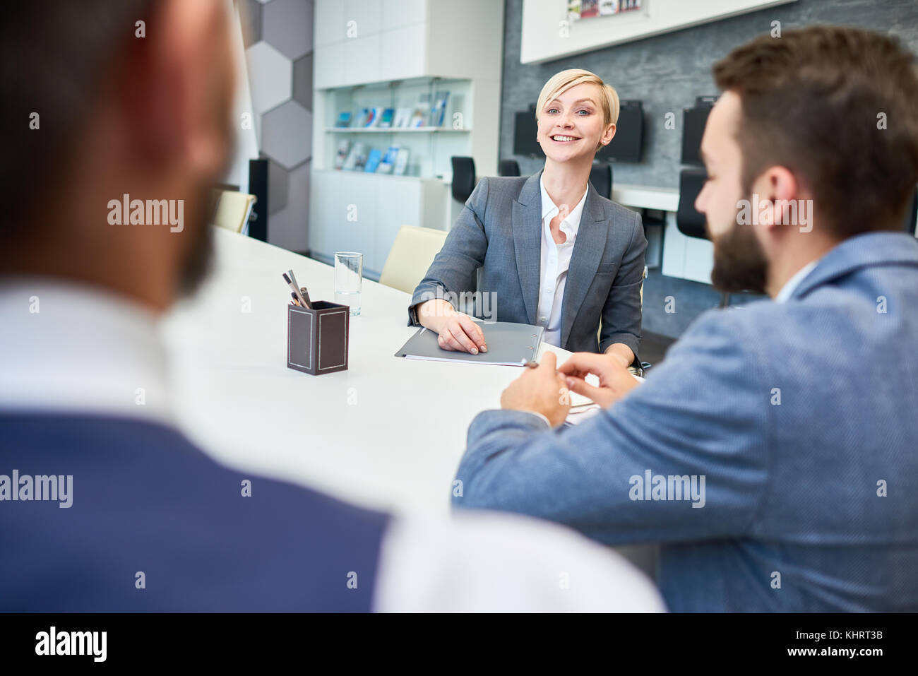 Portrait of young successful businesswoman talking to partners cheerfully sitting at meeting table in board room - Stock Image