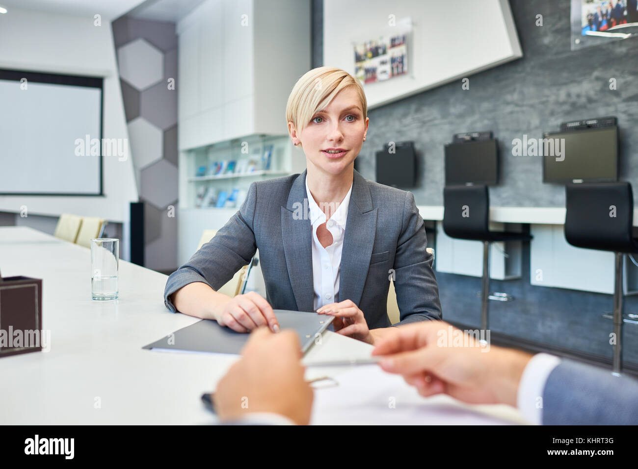 Portrait of successful blonde businesswoman talking to partners sitting at meeting table in board room presenting - Stock Image