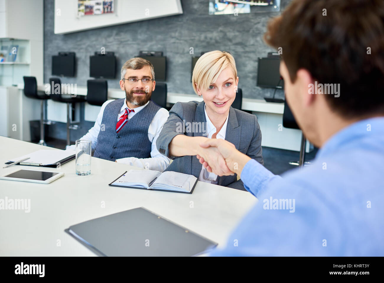 Portrait of young successful businesswoman shaking hands with partners at meeting table in board room - Stock Image