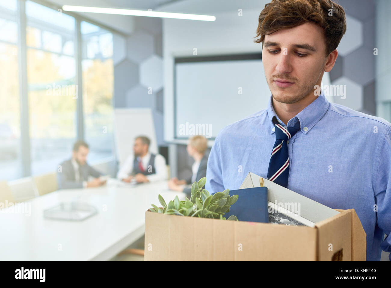 Portrait of sad young man holding box of personal belongings  fired from work in business company, copy space - Stock Image
