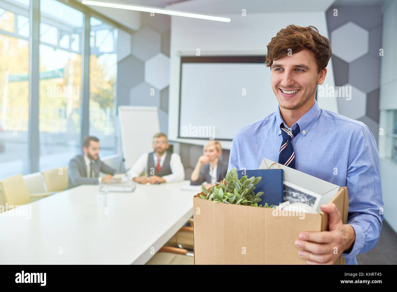 Portrait of smiling young man holding box of personal belongings being hired to work in business company, copy space - Stock Image