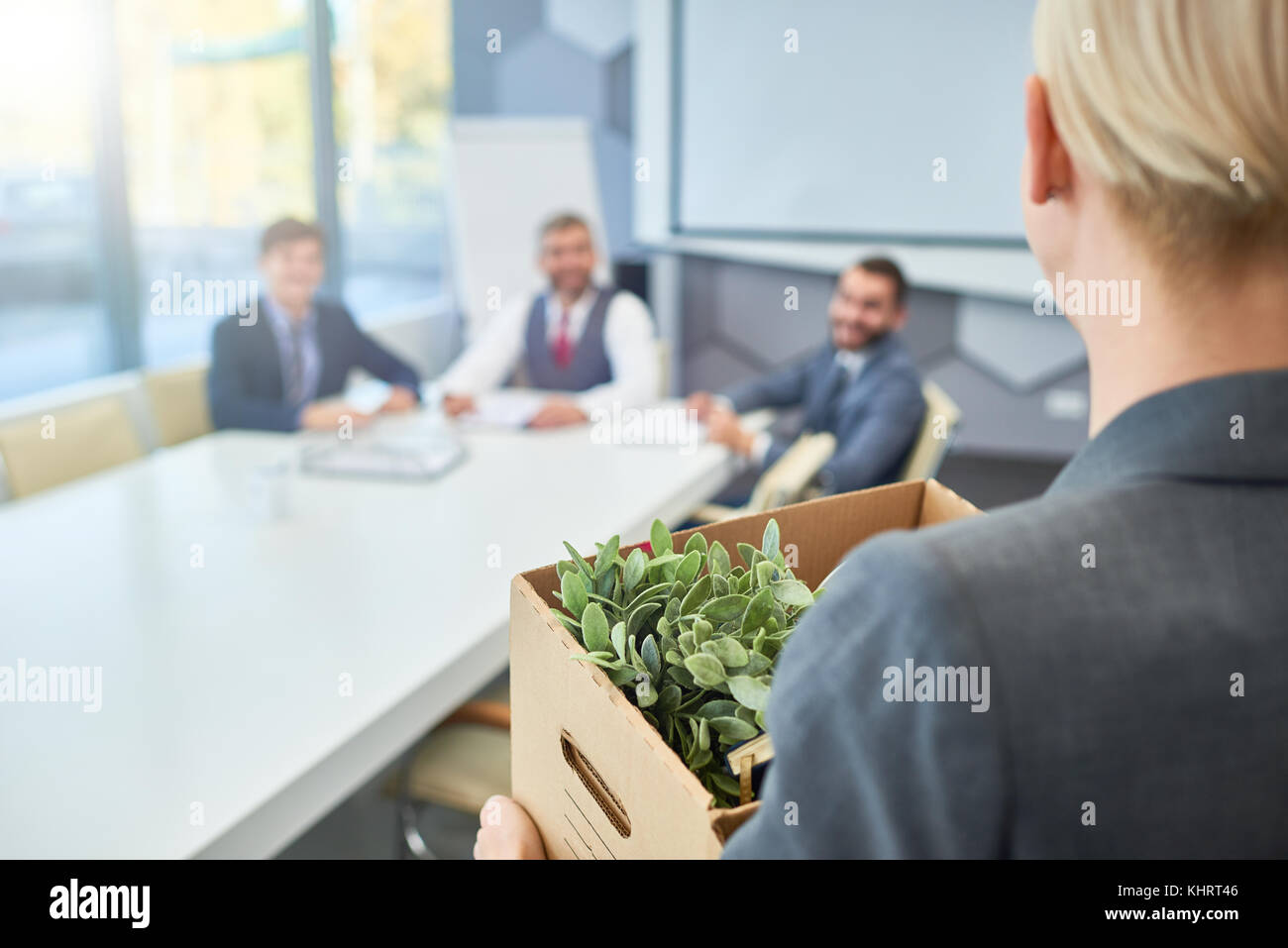 Rear view of unrecognizable young woman holding box of personal belongings coming to business interview in board - Stock Image