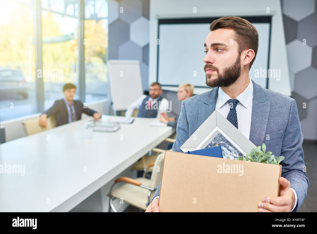 Portrait of sad bearded businessman holding box of personal belongings being fired from work, copy space - Stock Image