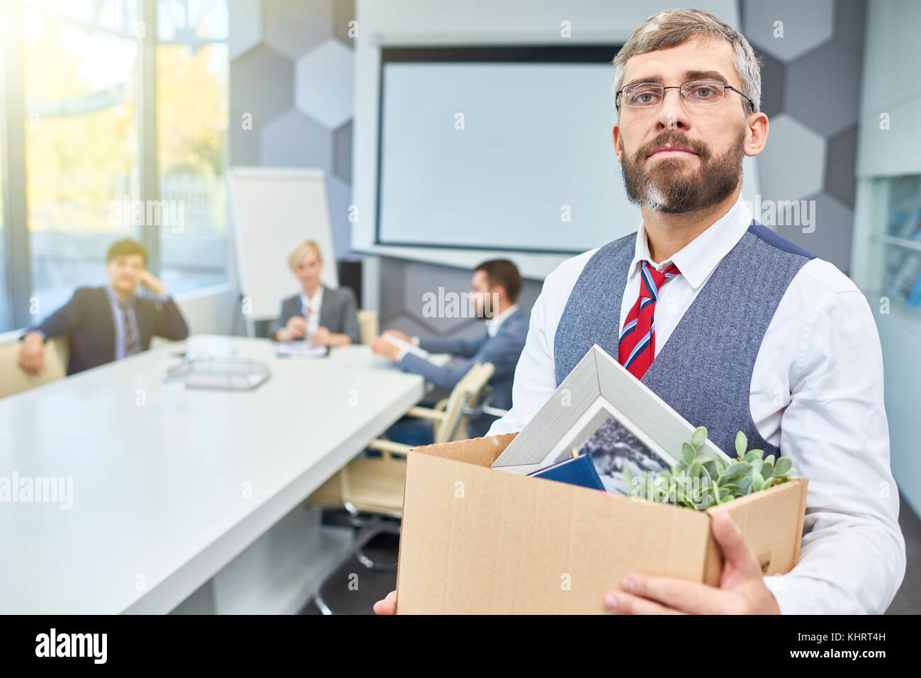 Portrait of mature bearded businessman holding box of personal belongings being fired from work in company, copy - Stock Image
