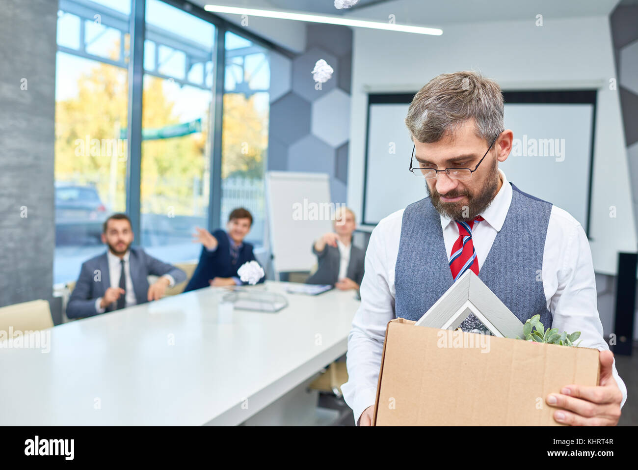 Portrait of depressed mature businessman holding box of personal belongings being fired from work in company, copy - Stock Image
