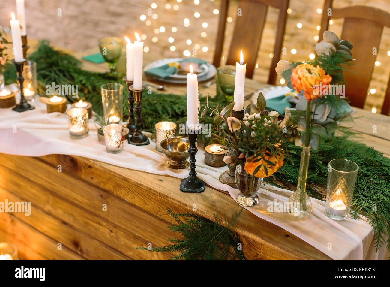 cosiness, celebration, silverware concept. lots of twinkle lights and burning candles illuminate decorated table - Stock Image