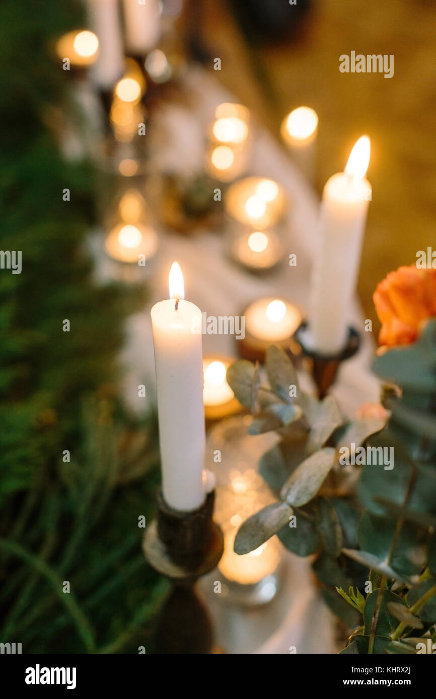wedding, cosiness, decor concept. close up of burning tall candles in the holders that are placed nearby with brunch - Stock Image