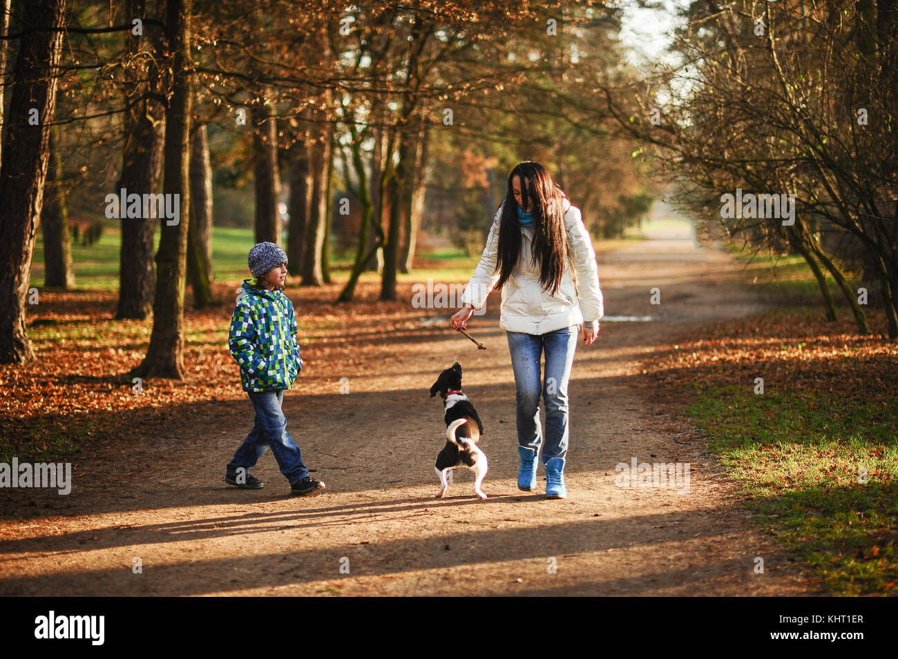 Mother and son walk their pet in the autumn Park. Young woman plays with a nice black-and-white doggie. Animal with - Stock Image