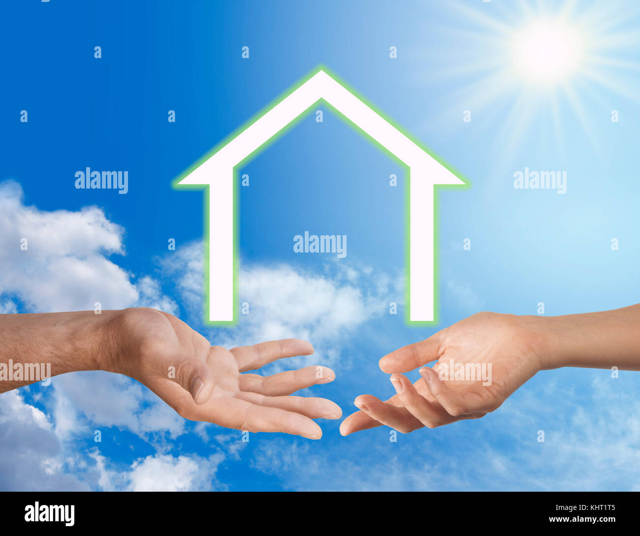 Our first ECO Home together - male and female hands in mid air against a sunburst and blue sky with a white house - Stock Image
