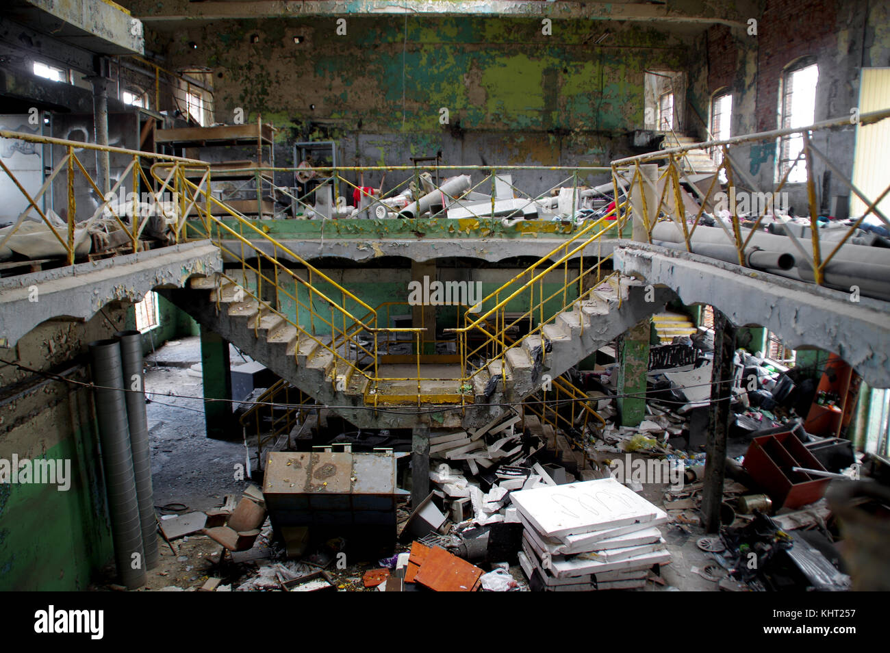 Mess and disorder in destroyed factory. Stairway in ruined industrial interior. - Stock Image