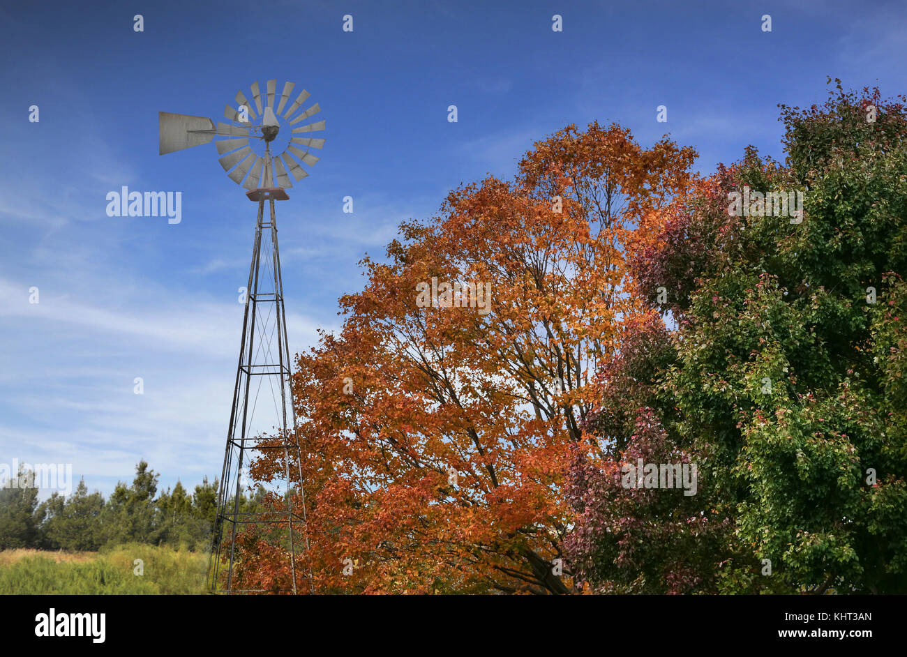 Typical NorthAmerican Countryside Landscape With Redish-Yellow Trees And Old Windmill - Stock Image