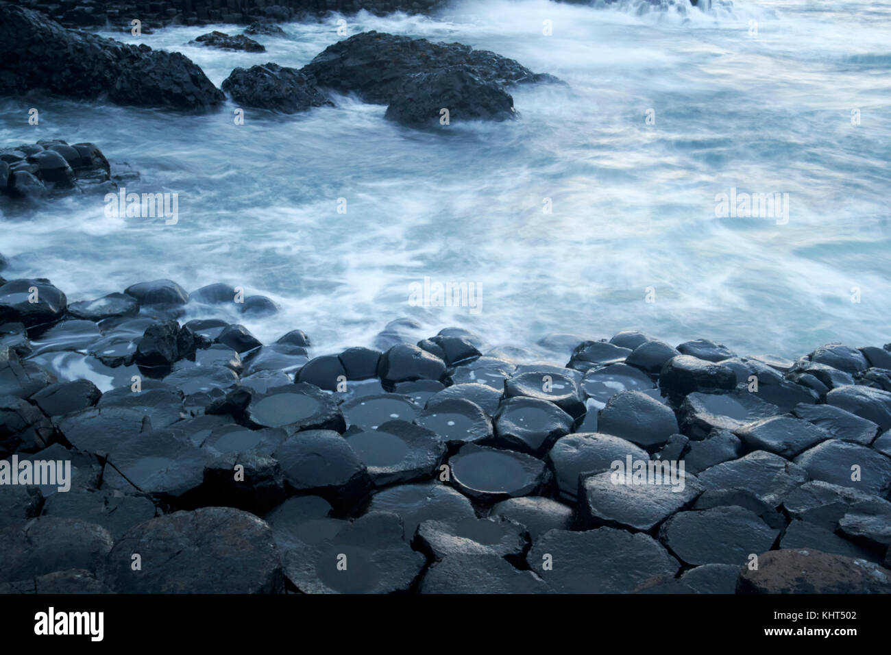 rocks in evening twilight with milky sea due to long exposure at the Giants Causeway county antrim northern ireland - Stock Image