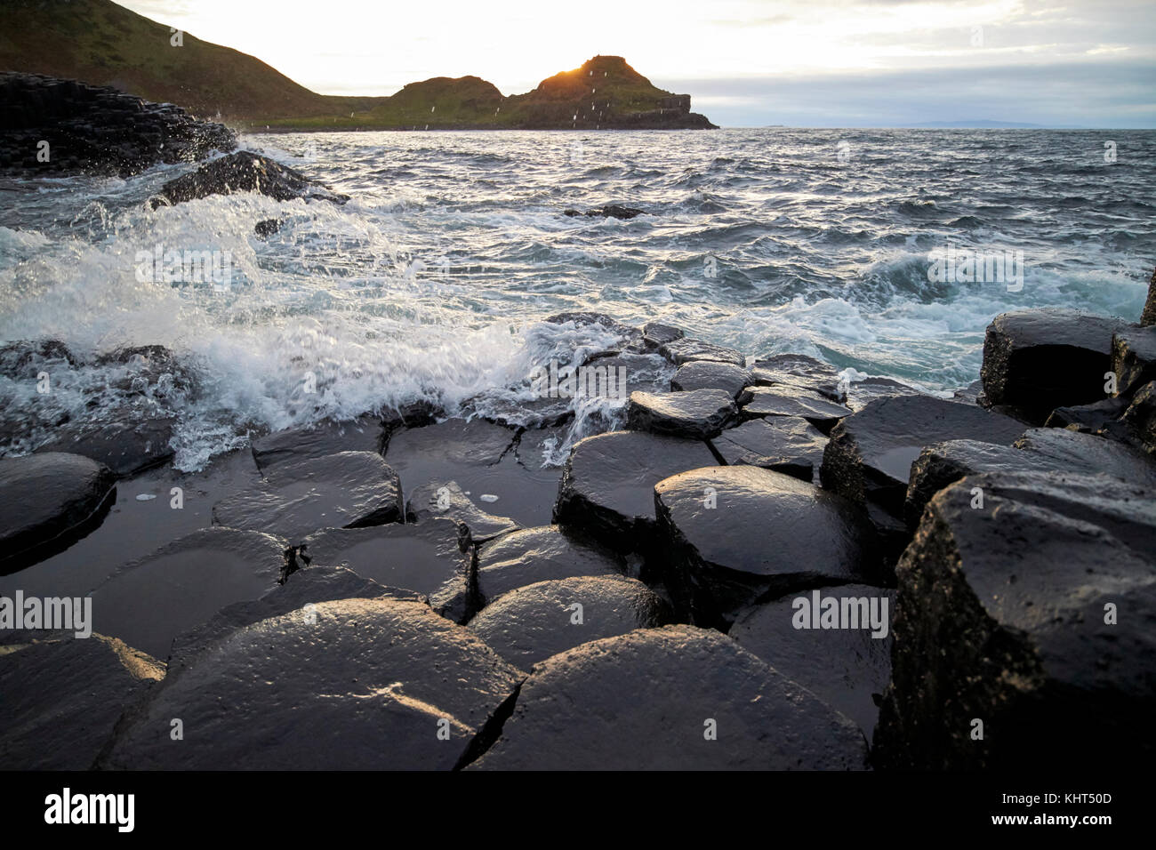 waves breaking over rocks sunset evening at the Giants Causeway county antrim northern ireland uk - Stock Image