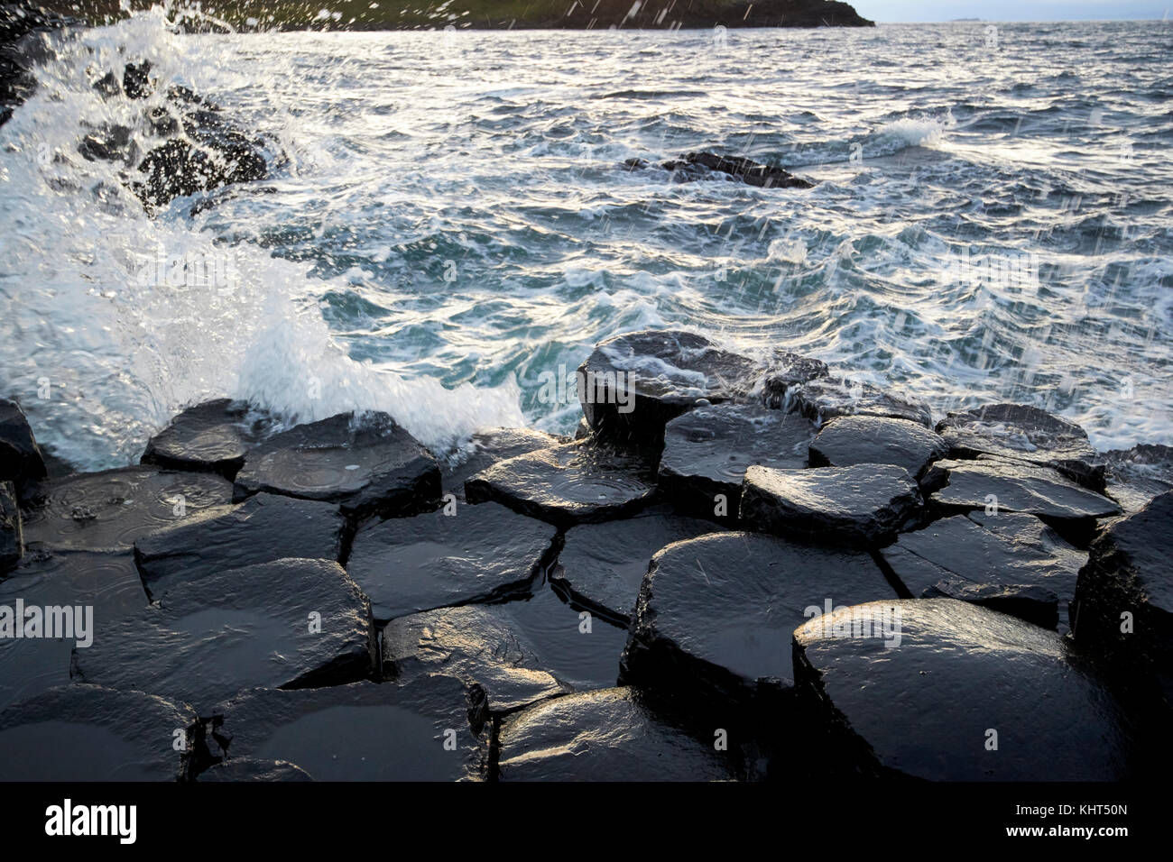 waves breaking over rocks at the Giants Causeway county antrim northern ireland uk - Stock Image