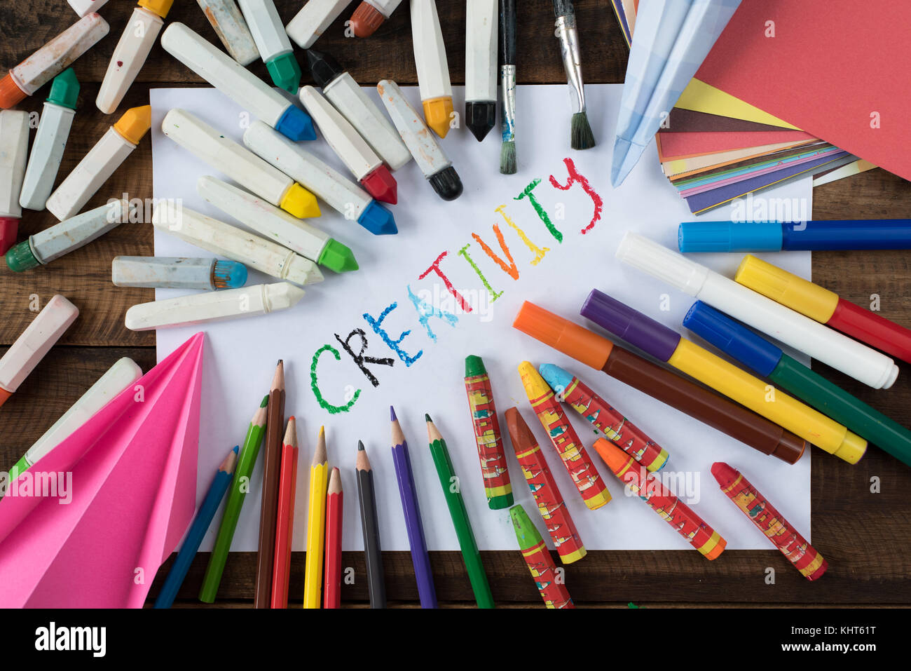 creativity concept - colorful paper, crayon, colorful pencil and paper with word CREATIVITY - Stock Image
