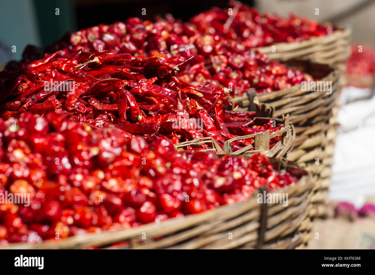 Dried Chili Peppers Bamboo Basket on wooden table,close up dried chili in basket close up red dried chili,Dried - Stock Image