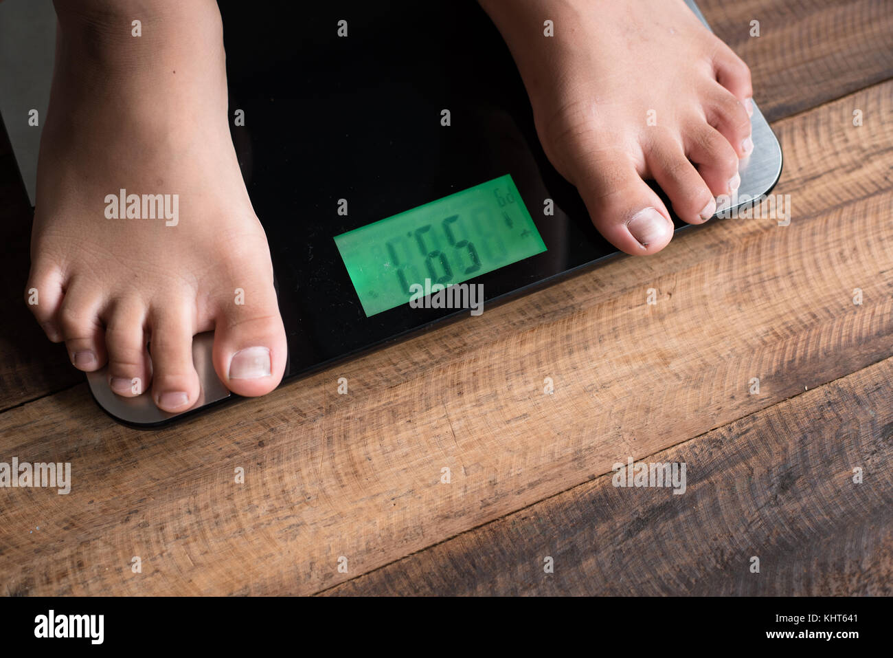 asian boy feet on a weighing scale - boy standing on weighing scale - Stock Image