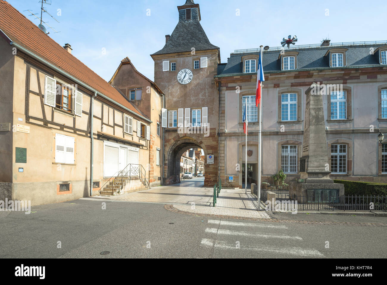 square with clock tower, flags, town gate and town hall of the village Rosheim, Alsace, France - Stock Image