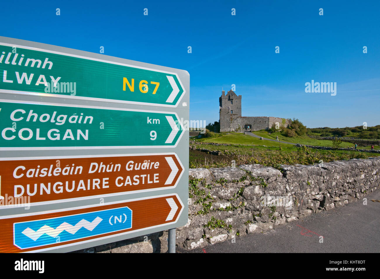 Road signs along the Wild Atlantic Way and Dunguaire castle, Kinvarra, County Galway, Ireland - Stock Image