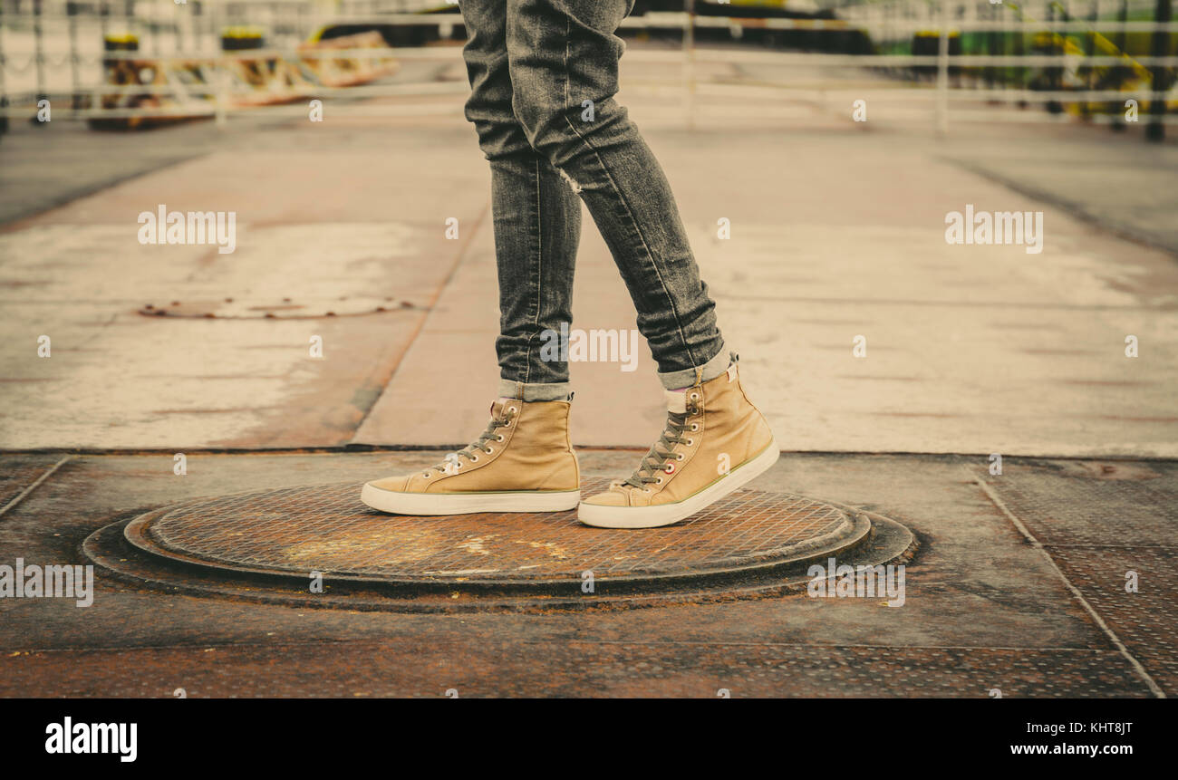 Male Legs In Grey Jeans And Canvas Boots Outdoor. Fashion Street Photo, color tone. - Stock Image