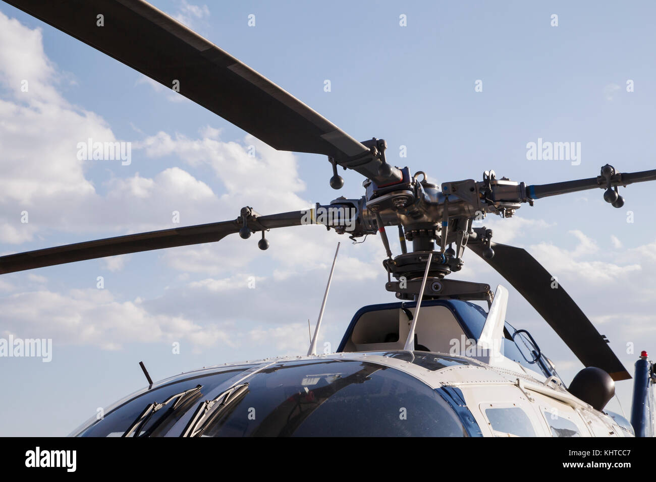 blades of a helicopter standing on land on a helipad - Stock Image