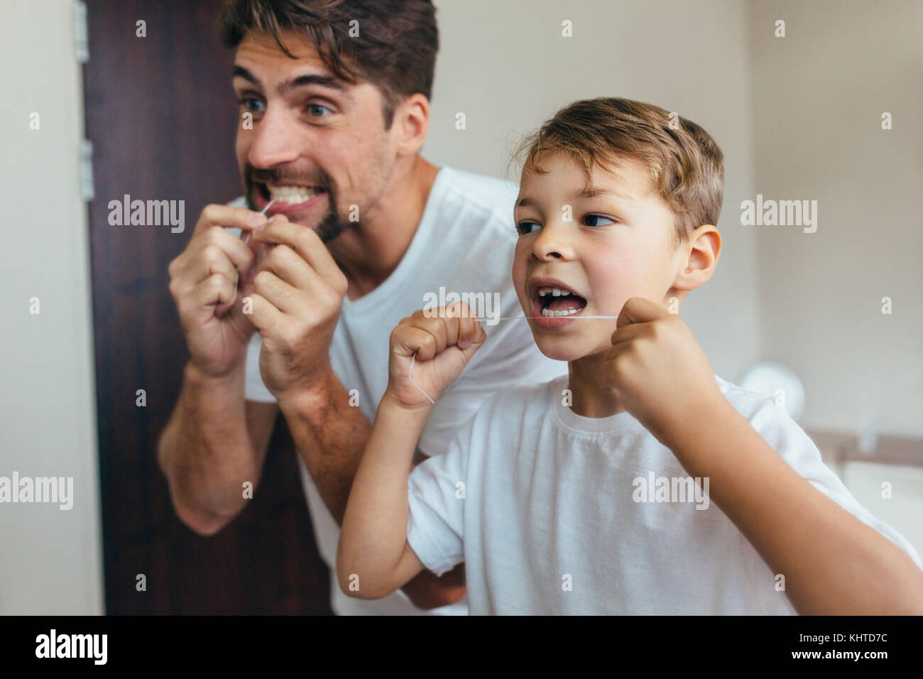 Little boy with his father in bathroom cleaning teeth with dental floss. Both looking in mirror and brushing teeth. - Stock Image