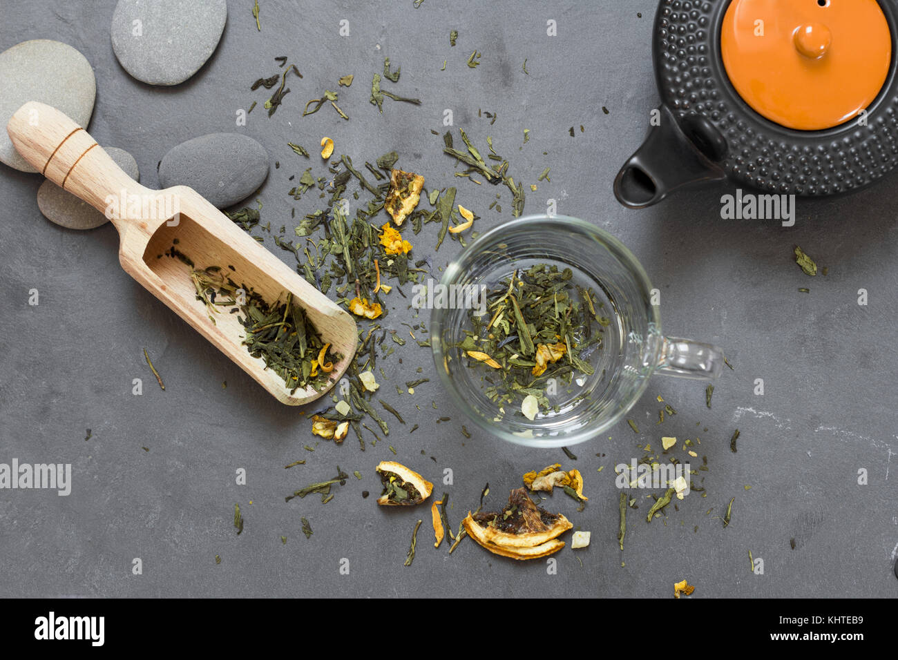 cup with dry green tea and tea pot - Stock Image