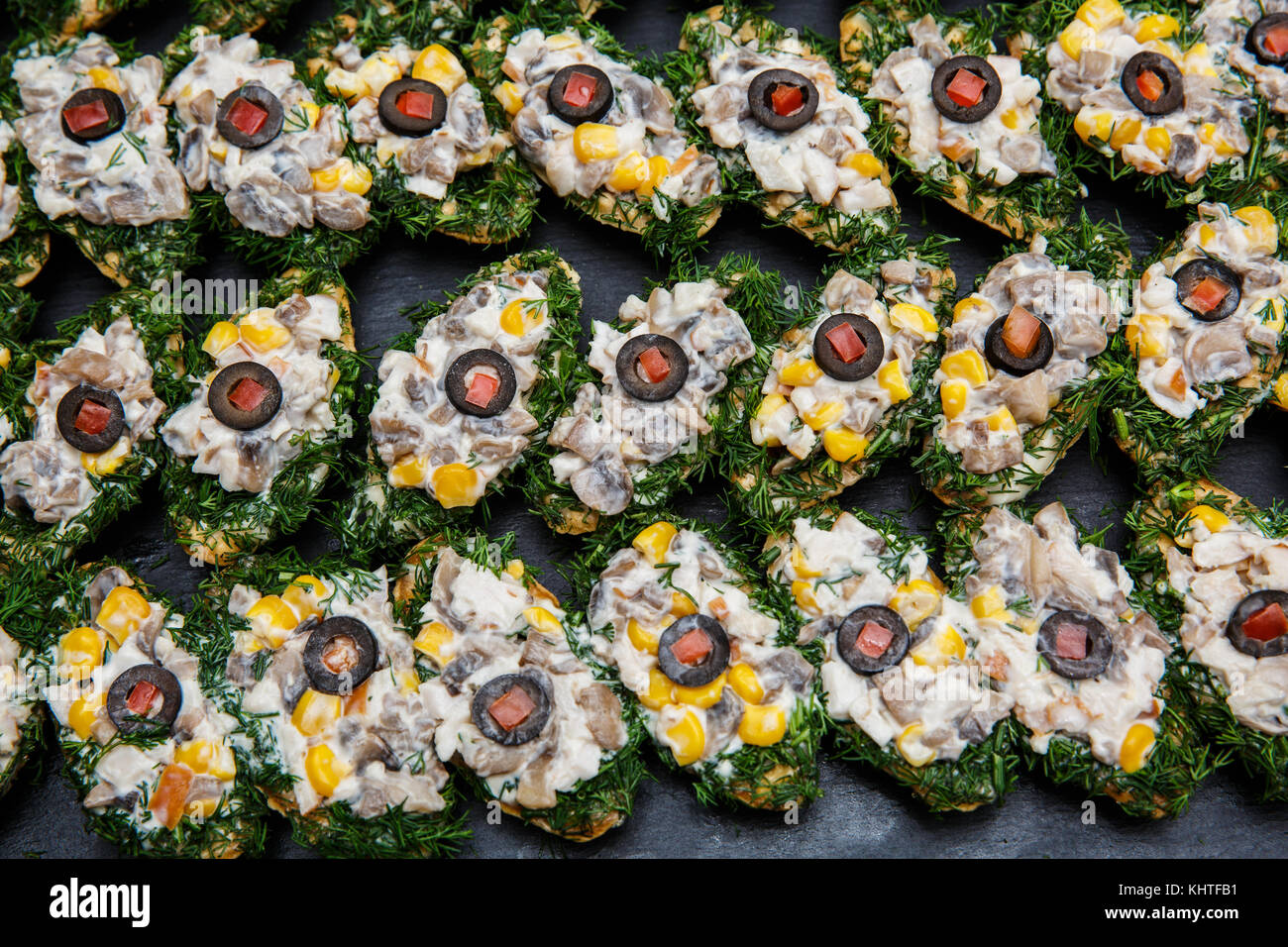 Selection of tasty bruschetta or canapes on toasted baguette with mushrooms, corn, fennel, olive, tomato, mayonnaise, - Stock Image