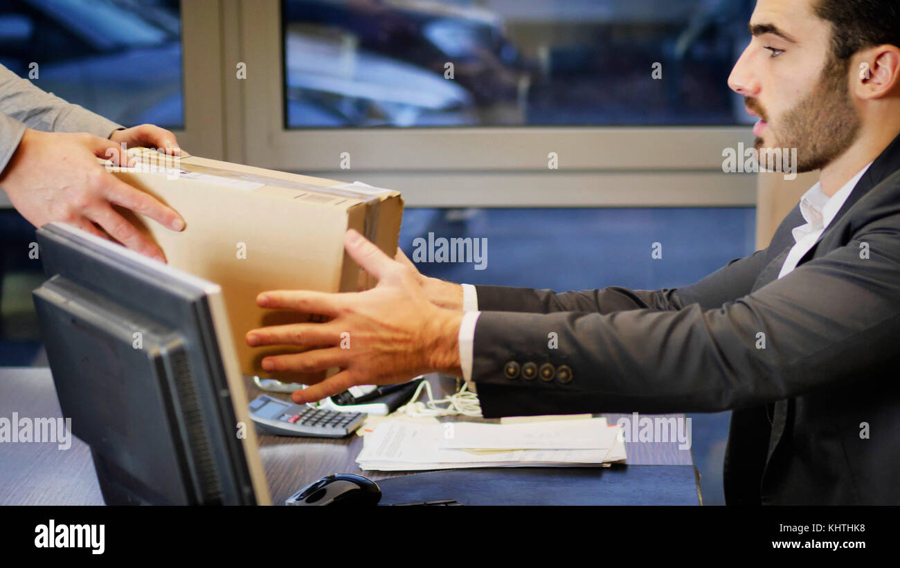 Businessman sitting in his office and looking at parcel delivered him by unrecognizable courier. - Stock Image