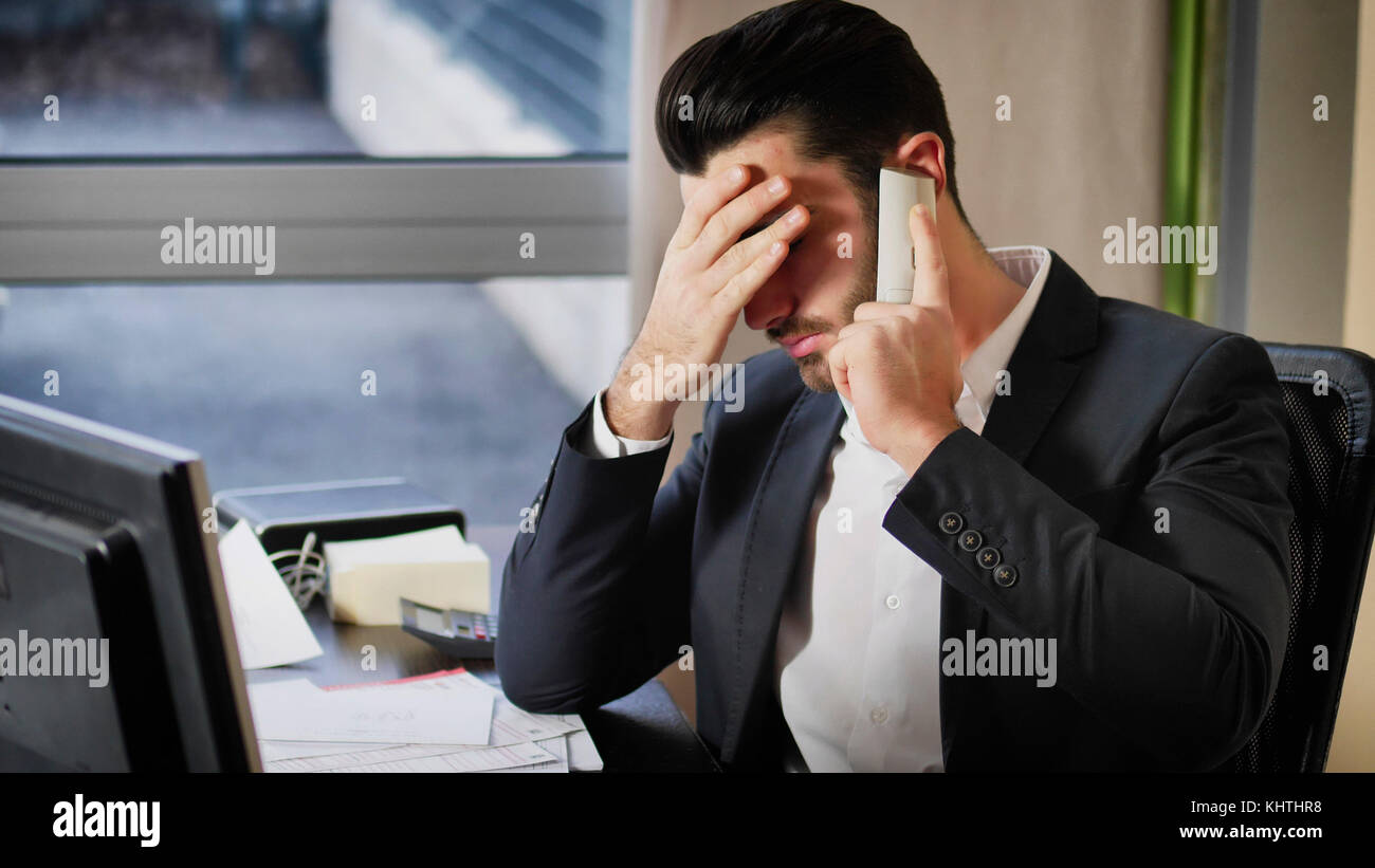 Serious attractive young businessman sitting at desk in office busy talking on phone and receiving upsetting news, - Stock Image