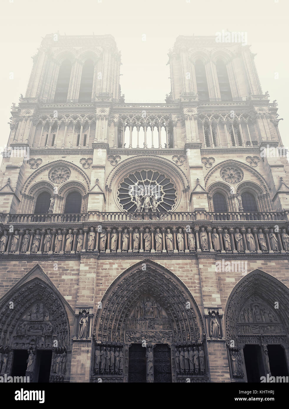 Facade of Notre Dame de Paris cathedral in a foggy morning. Stock Photo