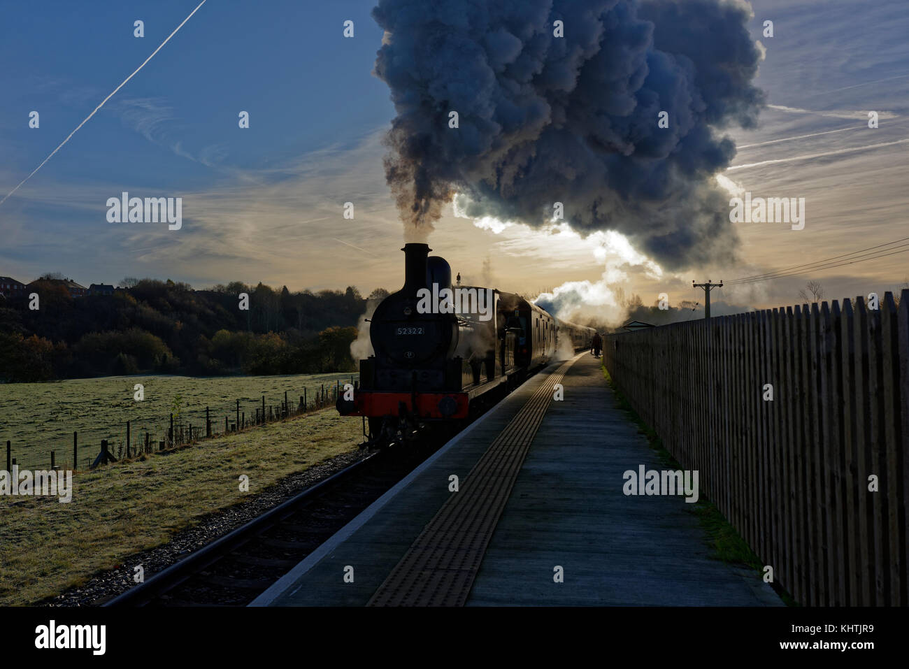 Steam train, black 0 6 0 locomotive pulling carriages arriving at burrs country park railway station on a frosty - Stock Image