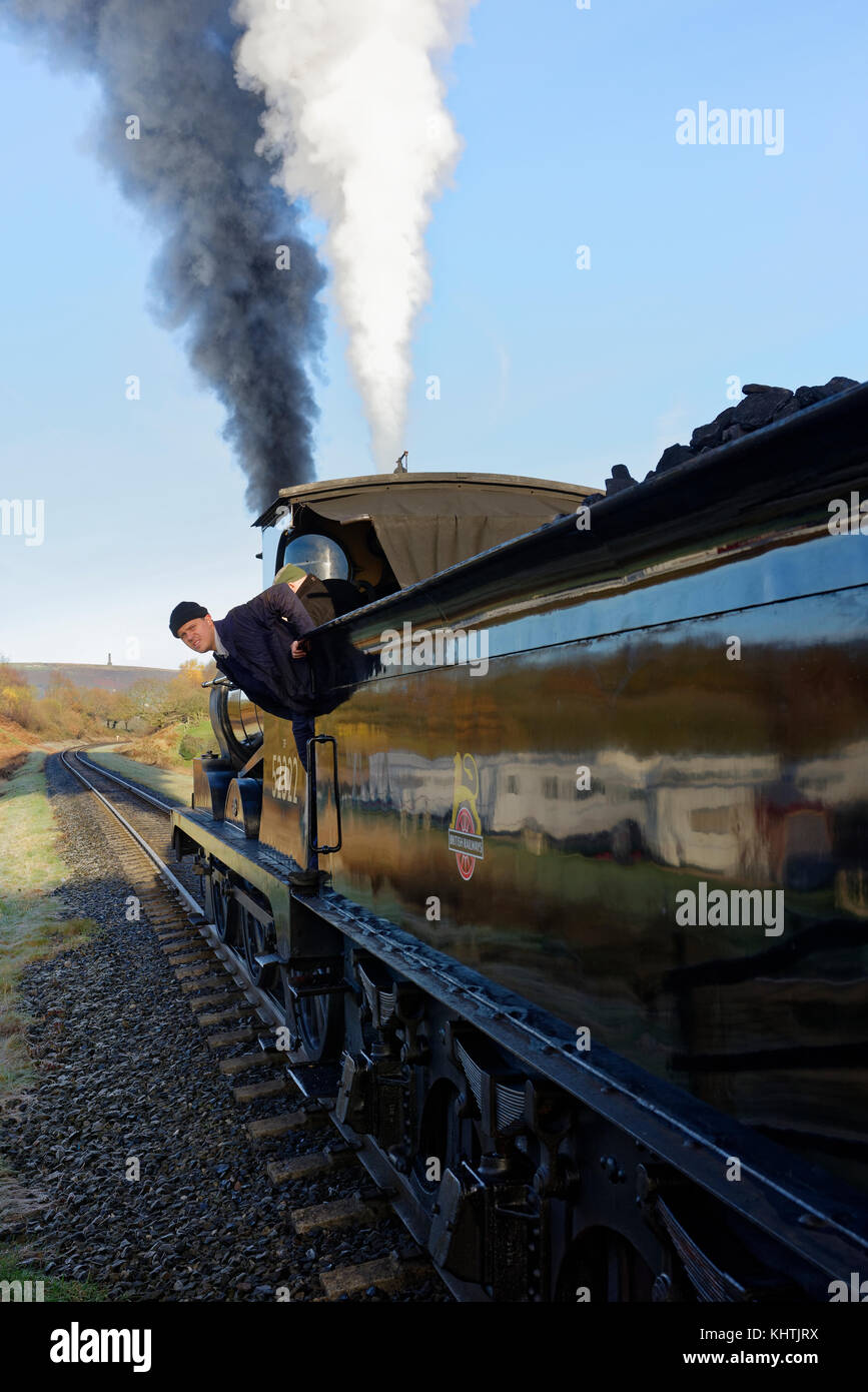Black steam train, 0 6 0 locomotive waiting to depart from burrs country park railway station, driver looking back, - Stock Image