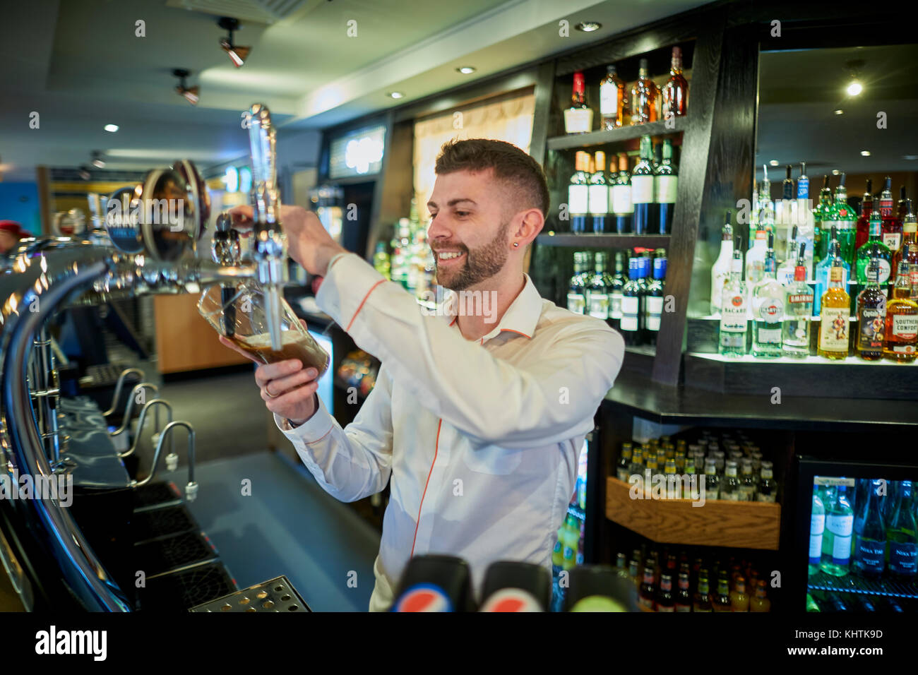 A barman pulling a pint at Marston's The Old Duke pub in Southport in Merseyside - Stock Image