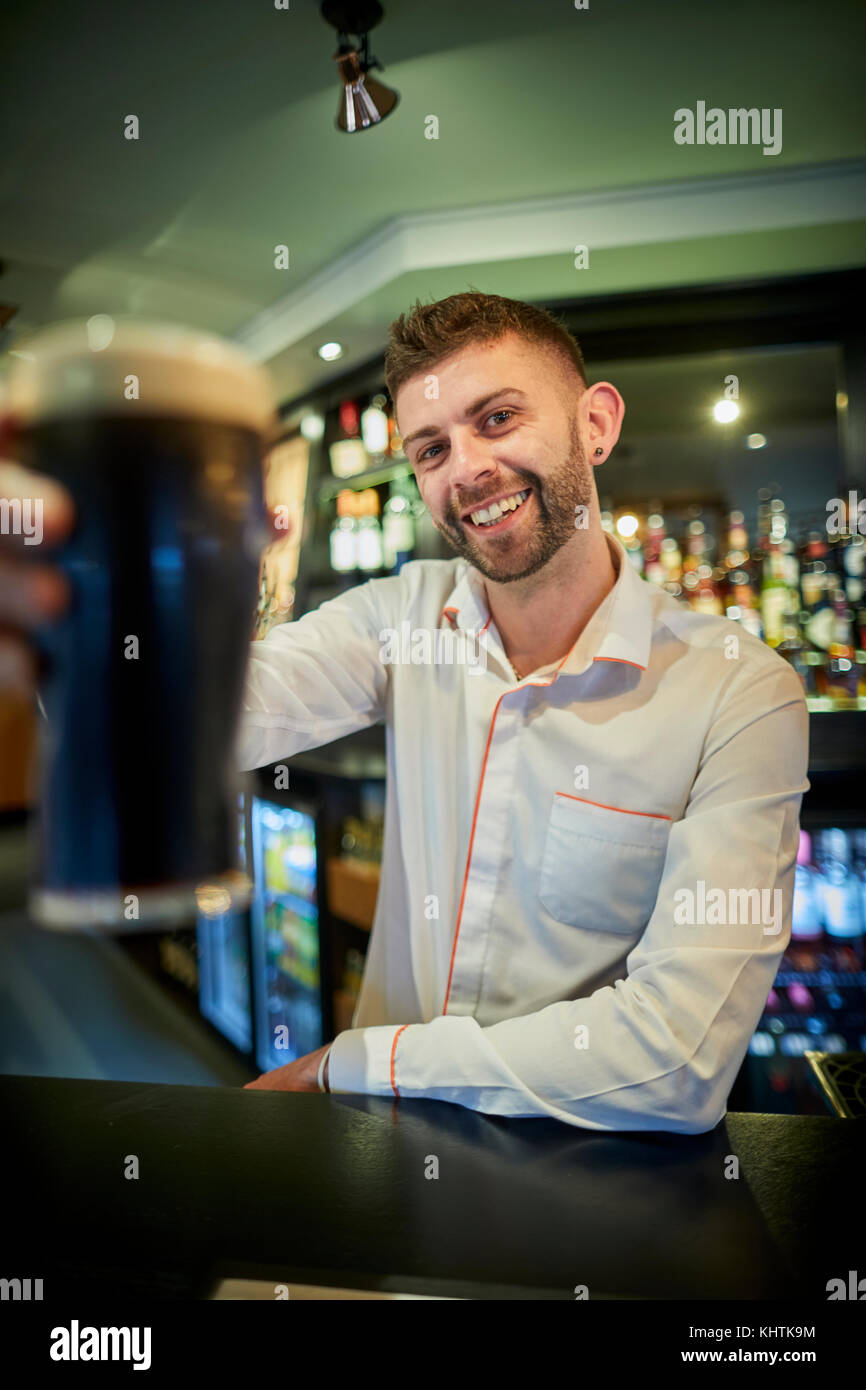 A barman holing a pint at Marston's The Old Duke pub in Southport in Merseyside - Stock Image