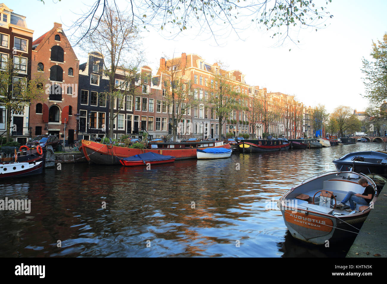 Typical houses and barges on the Prinsengracht canal, in Autumn, in Amsterdam, the Netherlands - Stock Image