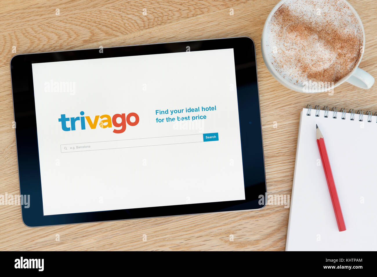 The Trivago website features on an iPad tablet device which rests on a wooden table beside a notepad and pencil - Stock Image
