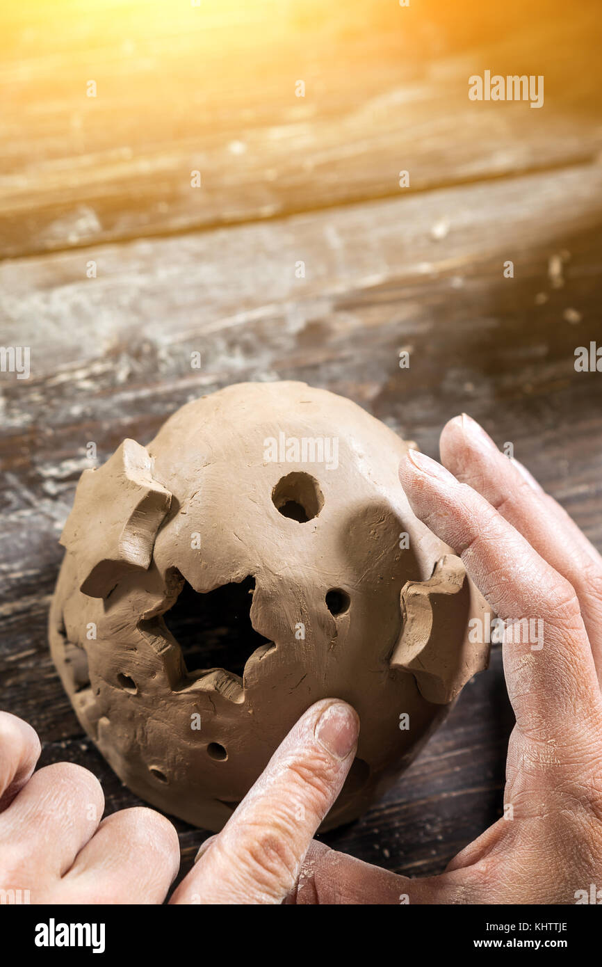 Close-up of a woman potter sculpts a brown clay candlestick in the shape of a ball with asterisks and a month on - Stock Image