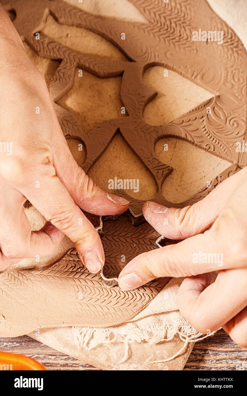Close-up of a young woman potter making New Year toys made of clay using metal molds: hearts, asterisks, small fish, - Stock Image