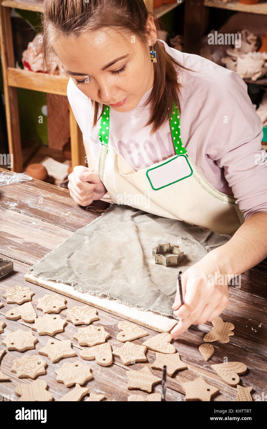 A close-up of a dark-haired woman potter makes New Year's toys from scorch clay using metal molds: hearts, asterisks, - Stock Image