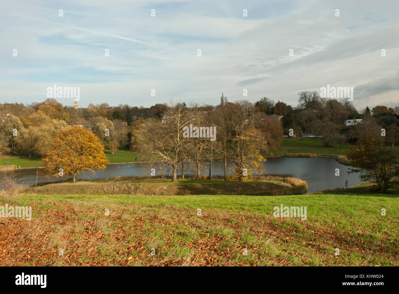 View across the Model Boating Pond, Hampstead Heath with warm autumn colours of the lake, trees and meadow. Highgate - Stock Image