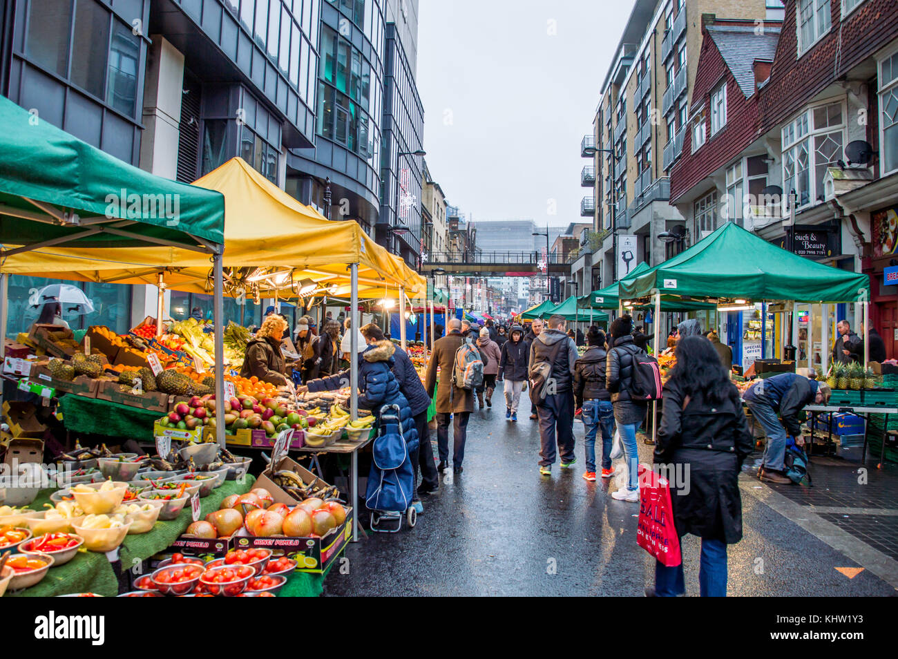 Croydon Surrey street market on a rainy day with sellers selling fruits and vegetables - Stock Image