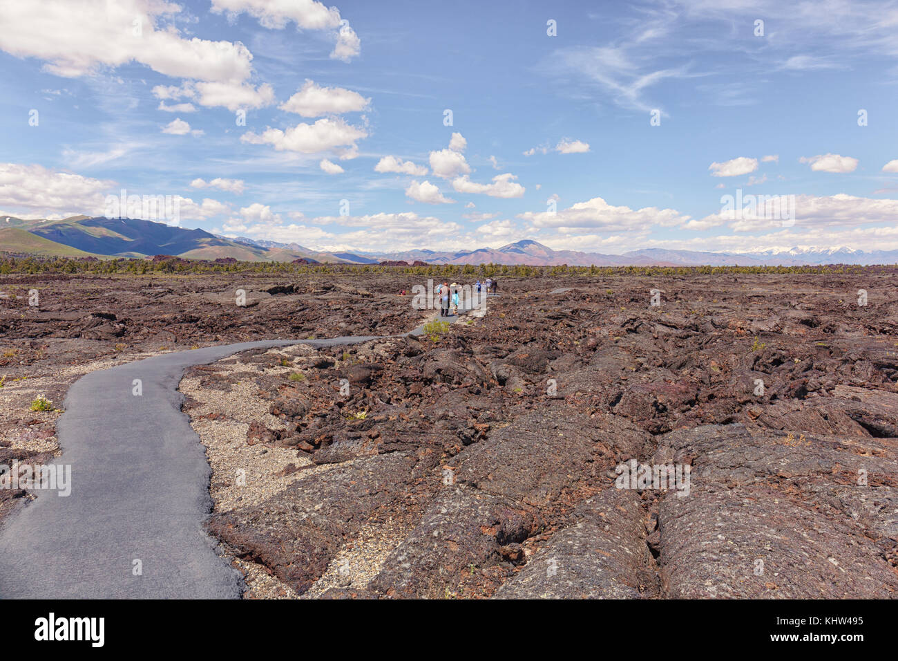 Tourists are hiking on an asphalt path on top of the lave flows of Craters of the Moon National Monument & Preserve Stock Photo