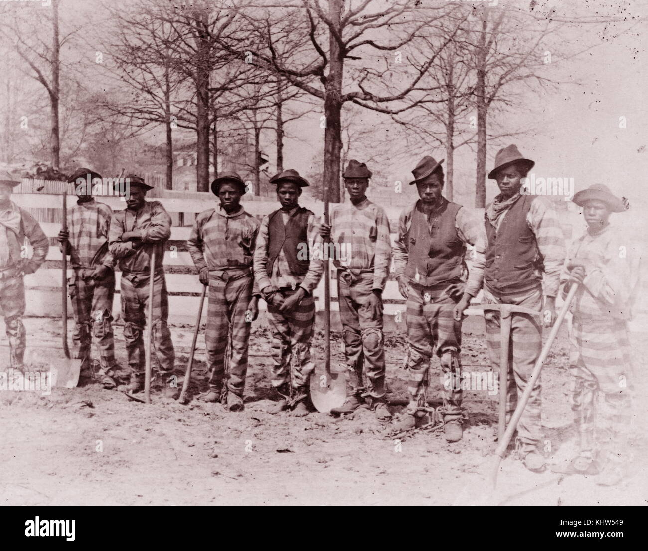 Photographic print of Nine African American men posed, standing along fence. Dated 19th Century - Stock Image